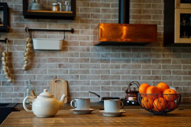 Sfondo per la cerimonia del tè all'interno della zona cucina in una casa accogliente. gli sfondi della teiera con le tazze sono sul tavolo in attesa del tè con gli ospiti. concetto di comfort domestico e relax. copia spazio