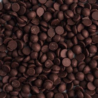 Texture di sfondo gocce di cioccolato da vicino. pezzi di cioccolato per la decorazione di dessert.