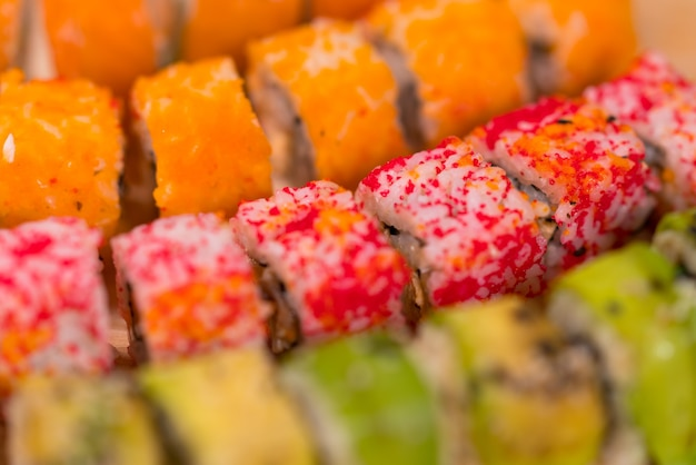 Trama di sfondo di rotoli di sushi colorati con pesce crudo fresco, riso e alghe in una visualizzazione full frame