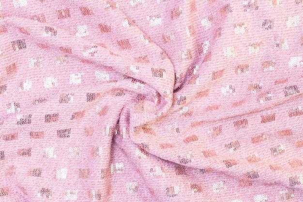 Trama di sfondo di morbido tessuto a maglia rosa con paillettes. bellissimo sfondo