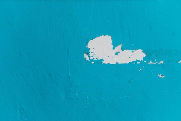 Texture di sfondo di un muro di cemento blu dipinto con vernice scrostata. primo piano, al chiuso