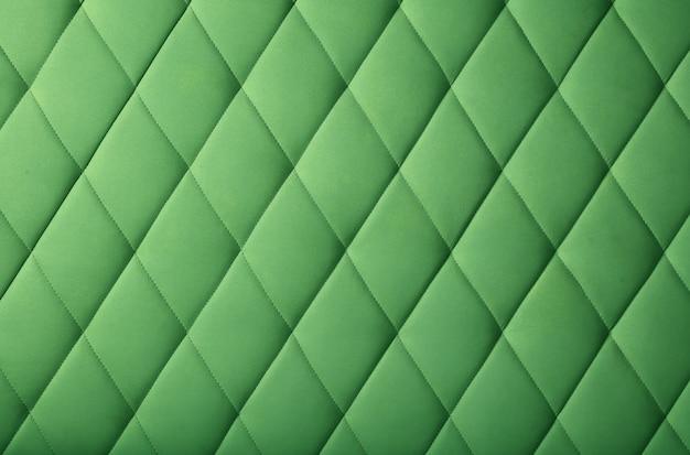 Texture di sfondo di mobili trapuntati morbidi in vera pelle verde scuro pastello o tappezzeria del pannello a parete con motivo a rombi profondi, da vicino