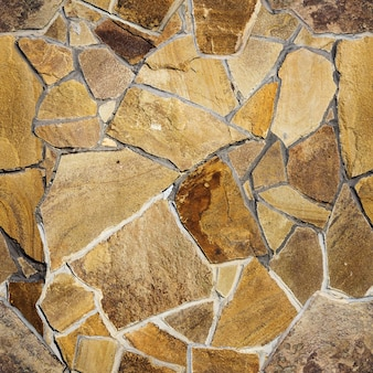 Sfondo e texture muro di pietra decorativo di colore rosso, bianco, giallo, arancione e marrone con muratura, modello senza soluzione di continuità
