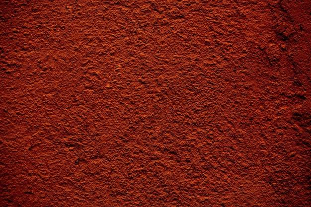 Trama di sfondo di un muro di cemento con finitura ruvida dipinto in un colore marrone rosso in una visualizzazione full frame.