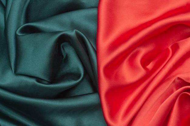 Trama di sfondo del tessuto di seta, i colori verde e rosso.