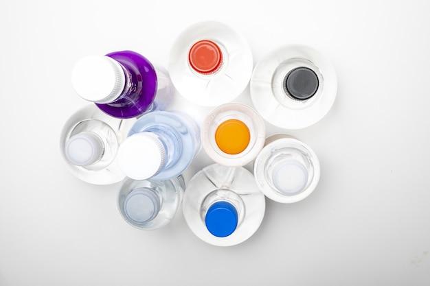 Sfondo di bottiglie d'acqua sferiche trasparenti con tappi colorati. vista dall'alto.