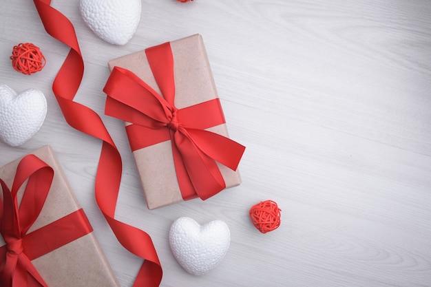 Sfondo per il giorno di san valentino biglietto di auguri concetto di giorno di san valentino nastri regalo rossi, regali, cuori su un fondo di legno. vista dall'alto.
