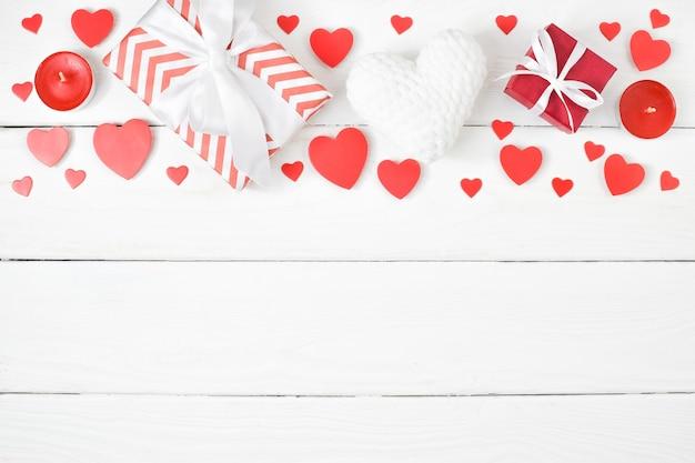 Sullo sfondo di san valentino. un regalo rosso si trova su uno sfondo di legno con cuori rossi. lay piatto. la vista dall'alto.