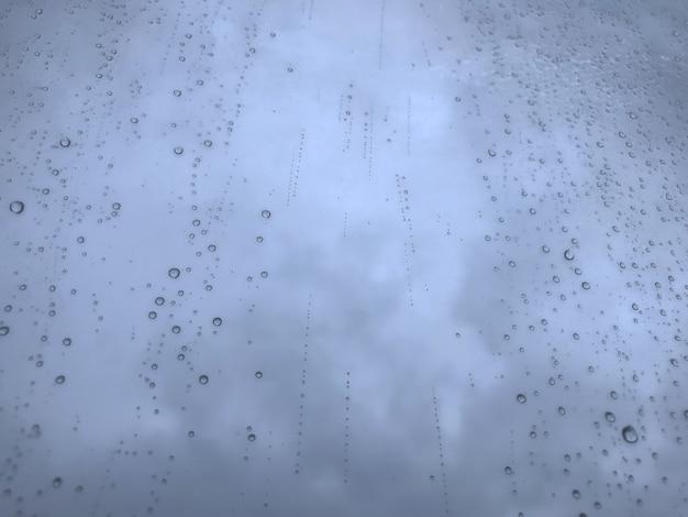Gocce d'acqua di sfondo. modello naturale di gocce di pioggia. gocce di pioggia sui vetri delle finestre. colpo astratto di gocce di pioggia su vetro. goccia di pioggia caduta astratta di pioggia su vetro. posto per un'iscrizione o un logo
