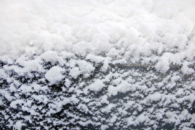 Sfondo di fiocchi di neve bianchi su vetro nero, primo piano