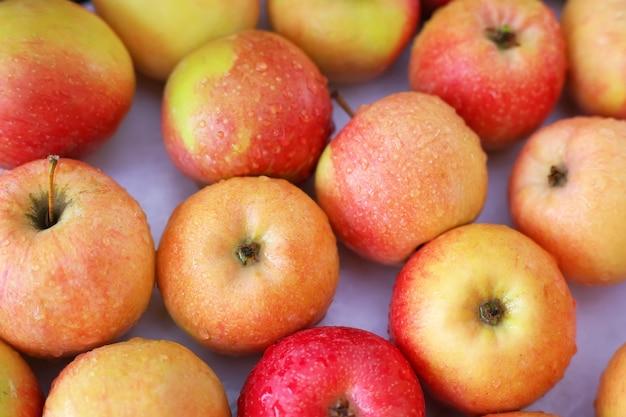 Sfondo con mele rosse succose deliziose fresche. deliziose mele agrodolci colorate nella scatola sul mercato