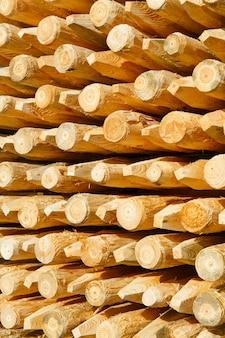 Sfondo con colonne di legno appena fatte. le colonne vengono utilizzate per l'installazione di recinzioni.