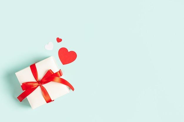 Sfondo con regalo e cuori con spazio libero per il testo su sfondo blu pastello