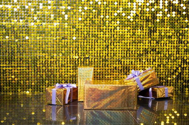 Sfondo con paillettes di paillettes dorate lucide con scatola di regali