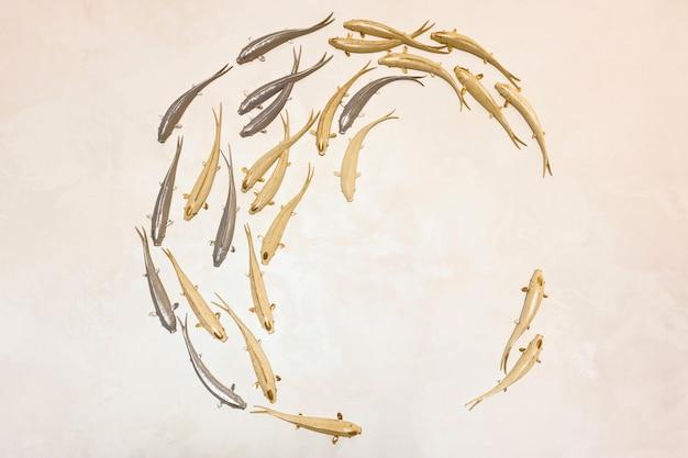 Sfondo con pesci d'oro e d'argento che nuotano in cerchio. pesce decorativo in gesso per creatività e design.