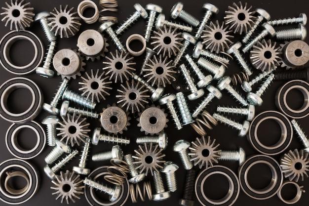 Sfondo con componenti meccanici, ingranaggi, molle, viti, oggetti industriali
