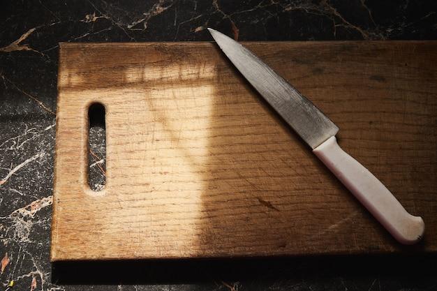 Fondo con il vecchio tagliere di legno che risiede nel tavolo da cucina alla luce solare del mattino.