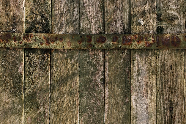 Sfondo con vecchia staccionata in legno con tenda in metallo. vecchia struttura di tavole.
