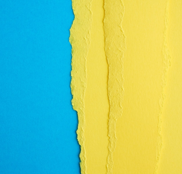 Sfondo con bordi strappati di carta gialla, sfondo blu, primi piani, copia dello spazio