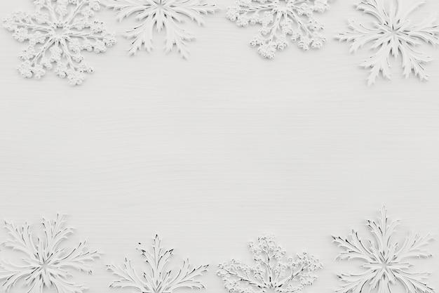 Sfondo con fiocchi di neve bianchi su legno bianco