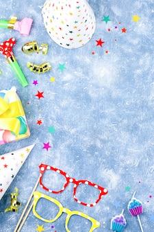 Sfondo con regali avvolti, coriandoli, cappelli da festa, decorazioni, copia spazio
