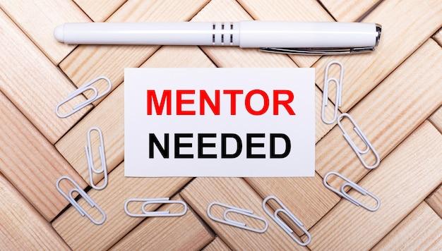 Su uno sfondo di blocchi di legno, una penna bianca, graffette bianche e un cartoncino bianco con il testo mentor needed. vista dall'alto