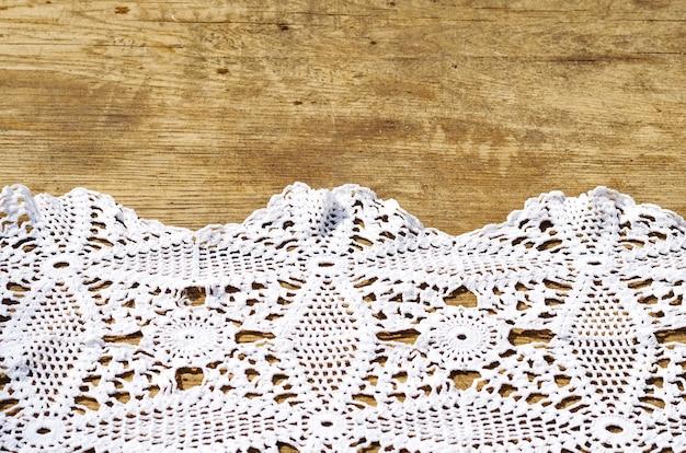 Sfondo di un tavolo in legno e un tovagliolo bianco all'uncinetto
