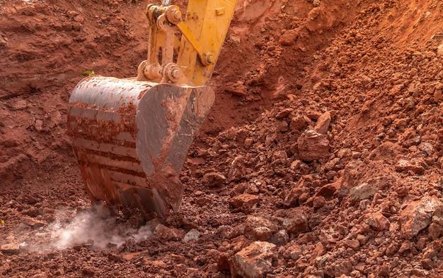 Benna dell'escavatore a cucchiaia rovescia che scava il terreno all'azienda agricola di agricoltura per fare lo stagno. escavatore cingolato che scava a strato di scisto. macchina da scavo. attrezzature per movimento terra. veicolo da scavo. attività di costruzione.