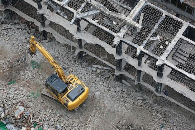 La demolizione del retroescavatore dell'edificio.