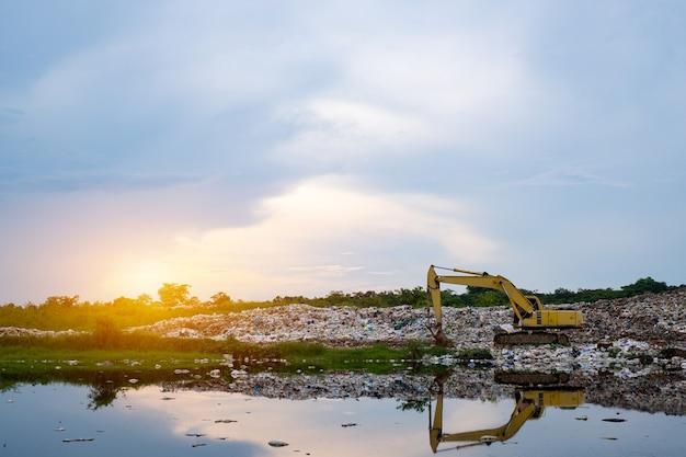 L'escavatore a cucchiaia rovescia sta sollevando immondizia nell'impianto di separazione dei rifiuti