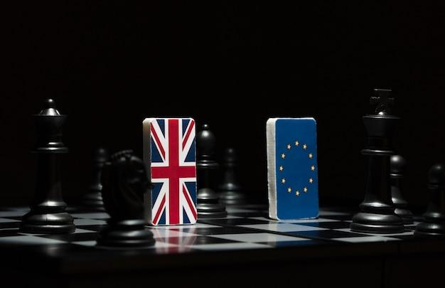Retroilluminato nelle ombre figure e bandiere dell'unione europea e della gran bretagna sulla scacchiera