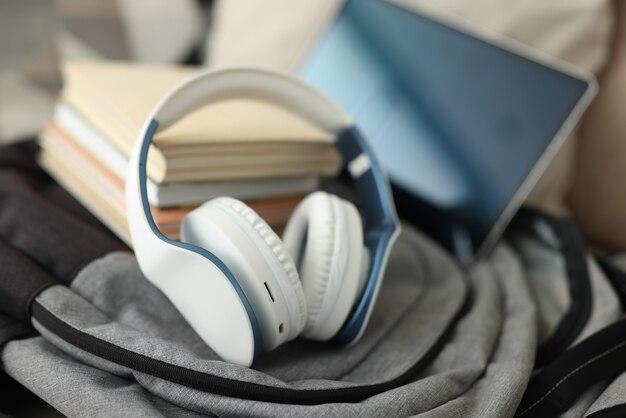 Sullo zaino ci sono cuffie, tablet e libri. lavoro a distanza e concetto di viaggio