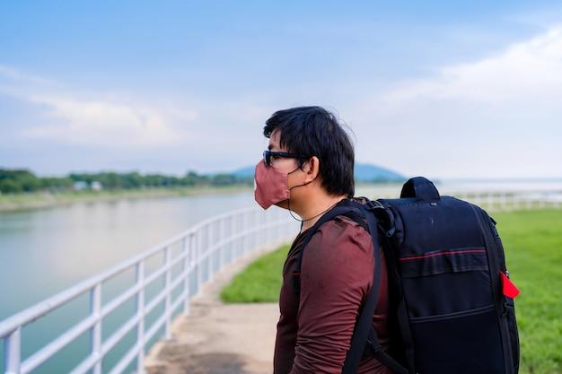 Zaino uomo asiatico indossa una maschera protettiva in tessuto durante il viaggio, l'uomo si rilassa in vacanza in piedi da solo guardando la vista del lago della diga