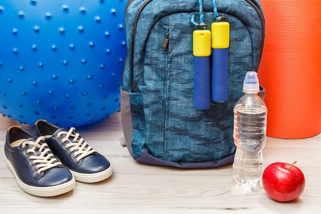 Zaino e diversi strumenti per il fitness in camera o in palestra su pavimento grigio