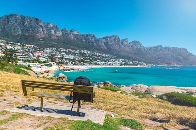 Zaino del viaggiatore solitario su una panchina in vista della splendida spiaggia di camps bay a cape town, sud africa