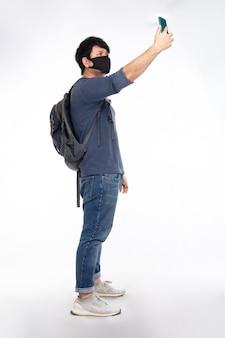 Uomo asiatico zaino in spalla con maschera nera alza lo smartphone per trovare un segnale