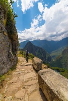 Viaggiatore con zaino e sacco a pelo che esplora le tracce di machu picchu, perù