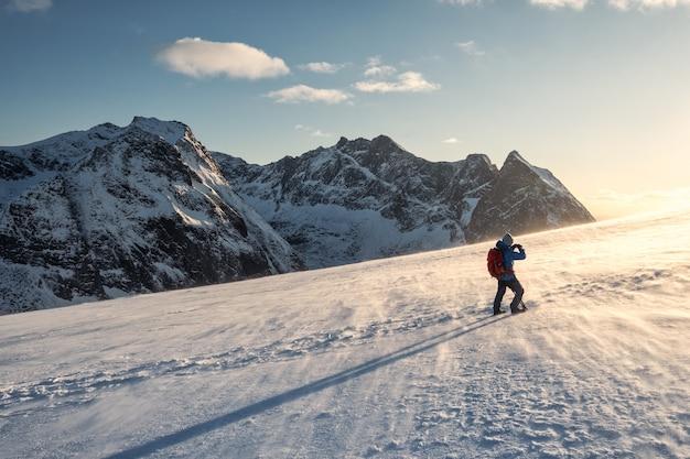 Backpacker uomo che fa un'escursione e scatta una foto sulla montagna di neve con la luce del sole che brilla al tramonto alle isole lofoten, norvegia