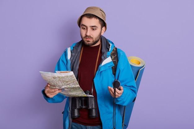 Zaino in spalla lettura mappa in viaggio mentre posa isolato su sfondo lilla