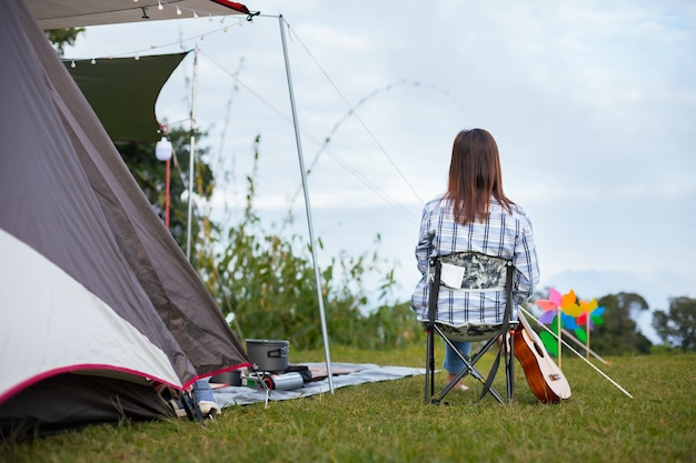 Retro della donna asiatica che si siede sulla sedia da picnic e si gode con la bellissima natura mentre si accampa con la famiglia nel campeggio.