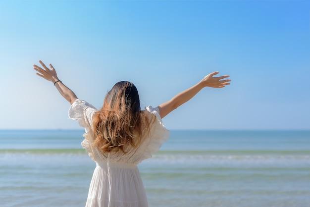 La parte posteriore della bella ragazza estende le braccia e sta in piedi sulla spiaggia in mezzo al cielo blu
