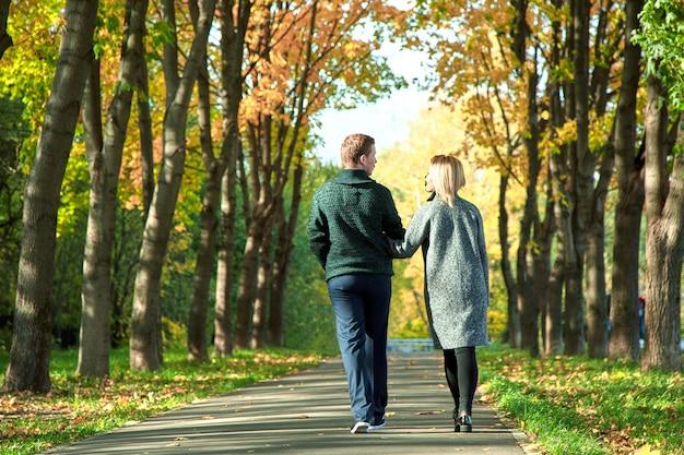 La parte posteriore della ragazza e del ragazzo si innamorano. concetto di amore, relazione, famiglia e persone - coppia felice camminando nel parco estivo