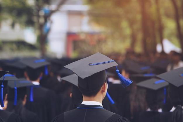 Cappelli di laurea sul retro durante i laureati di successo dell'inizio dell'università, congratulazioni per l'educazione del concetto. cerimonia di laurea, si sono congratulati con i laureati all'università durante l'inizio