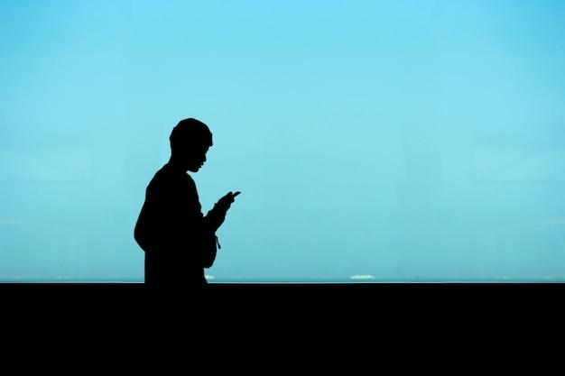 La parte dell'uomo che cammina e che gioca smart phone vicino alla finestra dell'alta costruzione.