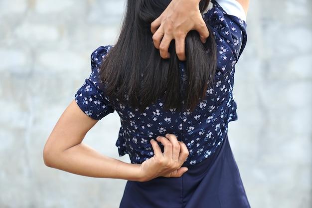Retro del concetto di dolore e dolore alla schiena della donna biancadonna asiatica pruriginosa nella parte posteriore