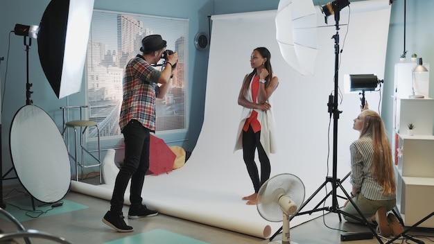 Backstage della sessione fotografica in studio moderno: assistente che regola i riflettori sul servizio fotografico