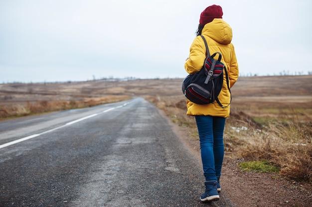 Backview di un turista femminile con uno zaino che indossa giacca gialla e cappello rosso cammina sulla strada.