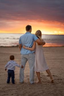 Backview di coppia felice che abbraccia sulla spiaggia al tramonto bambino in piedi da loro
