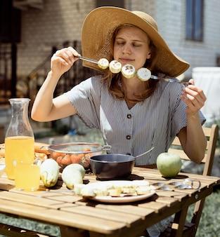 Barbecue in cortile. giovane donna in cappello estivo seduto al tavolo, mangiando verdure grigliate all'aperto Foto Premium