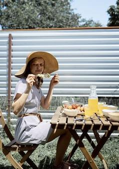 Barbecue in cortile. giovane donna in cappello estivo seduto al tavolo, mangiando verdure grigliate all'aperto